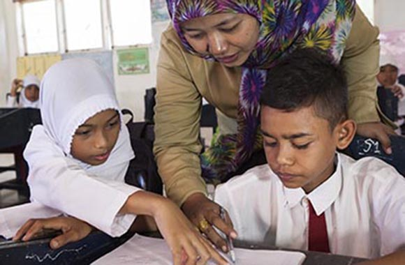 Lärare i Indonesien hjälper barn på skola som byggts upp med hjälp av Plan International.