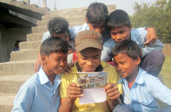 Pojke i Nepal läser brev från sin fadder