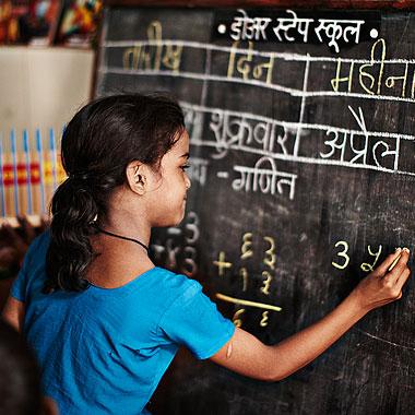Skolflicka skriver på svarta tavlan i Plan-skola i Mumbai