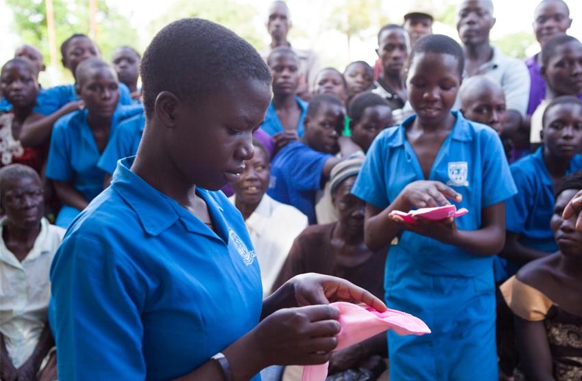 Flickor får titta och känna på återanvändningsbara mensskydd. Foto: Plan