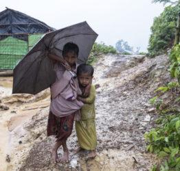 Två barn under ett paraply i flyktingläger i Bangladesh.