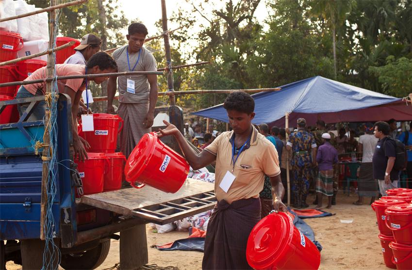 Planpersonal lastar röda tunnor med förnödenheter i Cox s Bazar i Bangladesh.