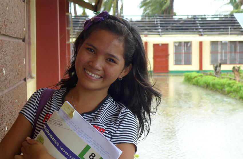 Mirinel är 17 år och lever i Filippinerna. Hon håller en bok i famnen och står framför en översvämmad gata.