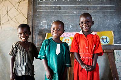 Tre skolbarn i Uganda