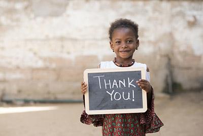 Flicka med Tack-skylt