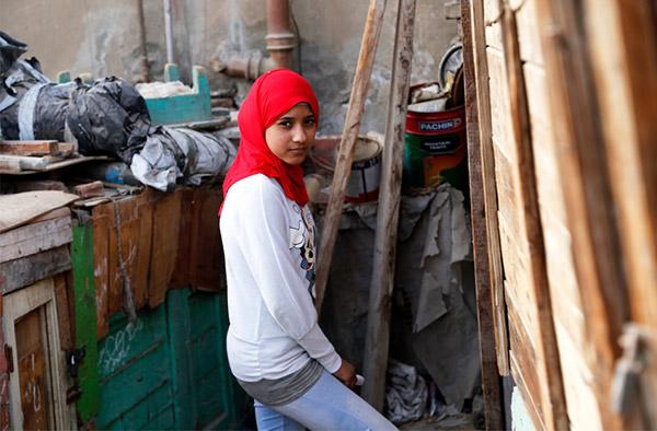 Amel i röd sjal, vit tröja och jeans. Hon kämpar mot könsstympning i Egypten.