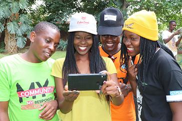 Fyra ungdomar tittar på en mobil